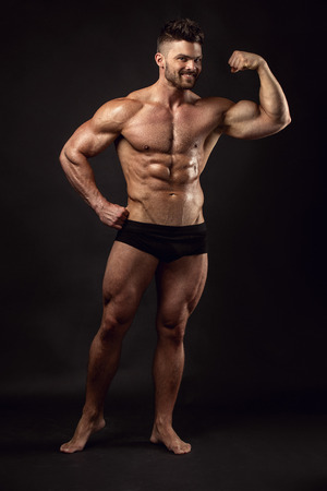 Strong Athletic Man Fitness Model Torso showing big muscles over black background