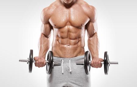 Foto de Muscular bodybuilder guy doing exercises with dumbbells over white background - Imagen libre de derechos