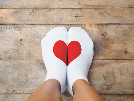 Selfie feet wearing white socks with red heart shape on wooden floor background. Love concept.