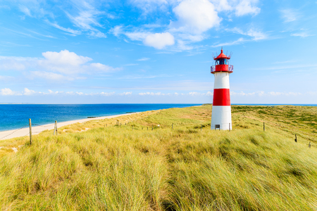 Photo pour Ellenbogen lighthouse on sand dune against blue sky with white clouds on northern coast of Sylt island, Germany - image libre de droit