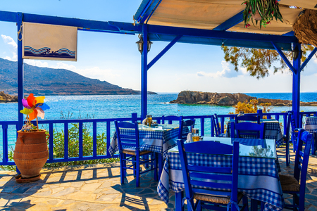 Foto de Terrace with tables in traditional Greek tavern with sea view in Lefkos village on Karpathos island, Greece - Imagen libre de derechos