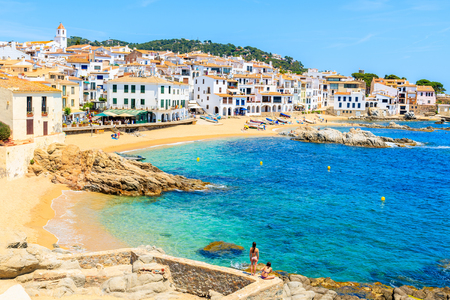 Photo pour Couple of young woman in swimsuits on amazing beach in Calella de Palafrugell, scenic fishing village with white houses and sandy beach with clear blue water, Costa Brava, Catalonia, Spain - image libre de droit