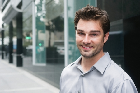 Portrait of a happy young businessman in suit standing outside office