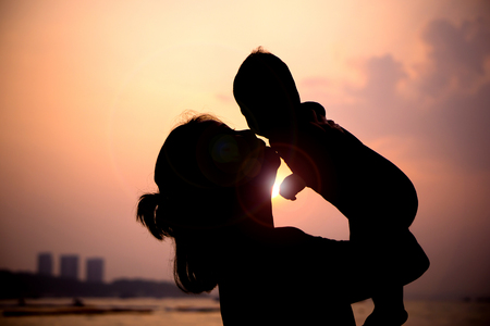 Photo pour Silhouette of mother  with her toddler against the sunset and lens flare - image libre de droit