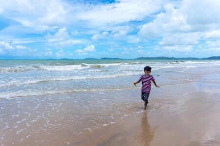Photo pour Asian kid enjoy playing in the sea and enjoying life during the summer holidays on the Phala Beach, Ban Chang District, Rayong, Thailand. - image libre de droit