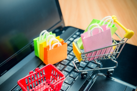 Photo pour Model colorful shopping bag in trolley and basket on laptop. Shopping at home or online internet shopping e-commerce idea concept. Worldwide commercial service. - image libre de droit