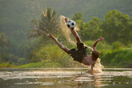 Movement of children playing succer in lake,focus on soccer ball