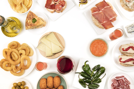 An overhead photo of Spanish tapas, forming frame on white with copy space