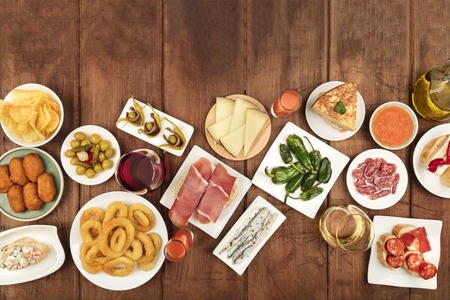 Spanish tapas foods on dark background with copyspace for text