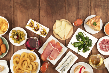 Spanish tapas food on dark background with wine and copy space