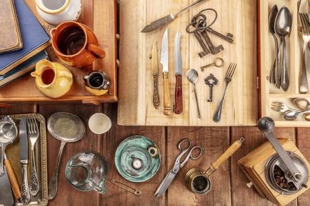 An overhead photo of many vintage objects, flea market stuff on a wooden background