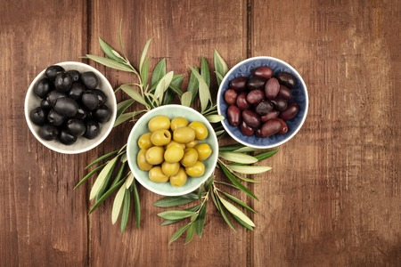 Photo pour Various olives in bowls with leaves, shot from the top on a dark rustic wooden background with a place for text - image libre de droit