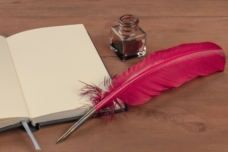 Foto de Writing Poetry. A photo of a quill with and ink well and an open book on a wooden table with a place for text - Imagen libre de derechos