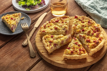 Photo for A photo of a quiche with a piece cut off, with wine and salad leaves on a dark rustic wooden background with a place for text - Royalty Free Image