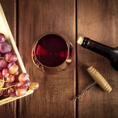Photo pour Wine Tasting. A photo of a red wine glass with a bottle, grapes, and a vintage corkscew, overhead square shot on a dark rustic wooden background - image libre de droit