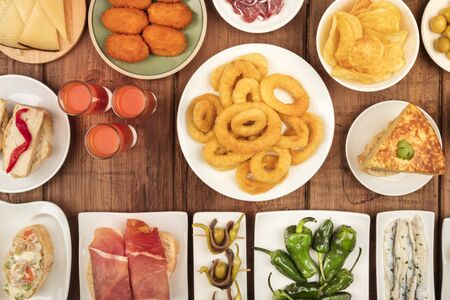 Spanish tapas, an overhead photo of a variety of snacks. Gazpacho, squid rings, tortilla, jamon, cheese etc, shot from the top on a dark rustic wooden background