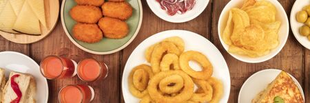 A panorama of Spanish tapas, an overhead photo of a variety of snacks. Gazpacho, squid rings, tortilla, cheese etc, shot from above on a dark rustic wooden background