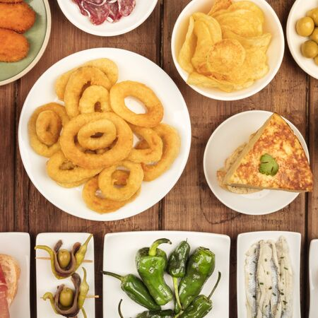Spanish tapas, a variety of snacks. Squid rings, tortilla, sardines, gildas, padron peppers, square overhead shot on a dark rustic wooden background,
