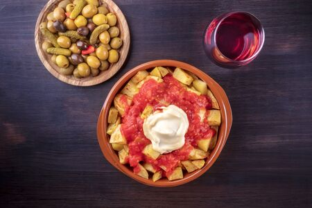 Photo for Patatas bravas, Spanish potatoes, with a glass of wine and olives, shot from the top on a dark background with a place for text - Royalty Free Image
