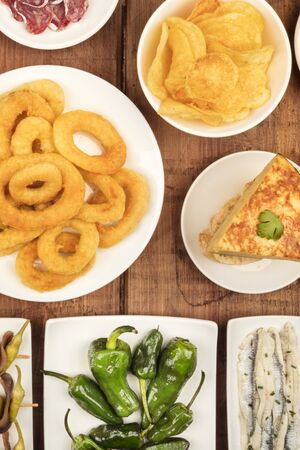 Spanish tapas, a variety of snacks. Squid rings, tortilla, sardines, padron peppers, top shot on a dark rustic wooden background,