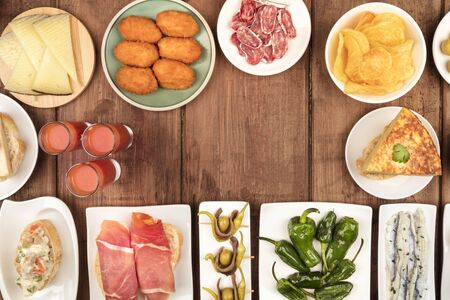 Spanish tapas, a variety of snacks, top shot. Gazpacho, tortilla, jamon, cheese etc, shot from the top on a dark rustic wooden background with a place for text