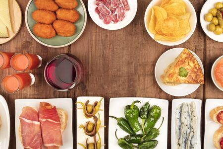 Spanish tapas, a variety of snacks, top shot. Gazpacho, tortilla, jamon, and wine, shot from the top on a dark rustic wooden background with copy space
