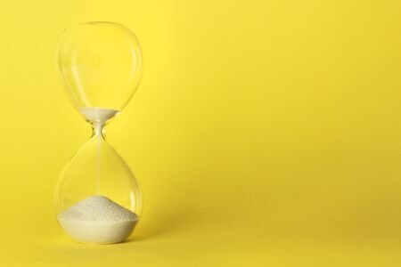 Foto de Time is running out concept. An hourglass on a vibrant yellow background with a place for text - Imagen libre de derechos