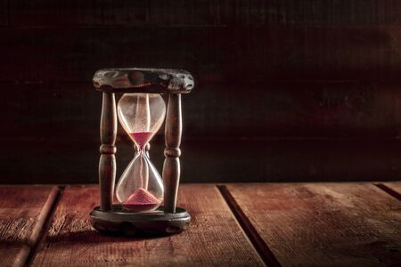 Photo pour Time is running out concept. An hourglass with sand falling through, on a dark wooden background with copy space - image libre de droit