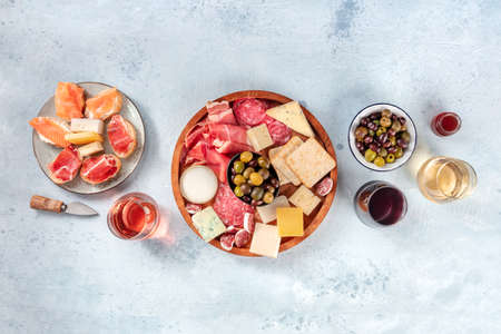Photo pour Charcuterie and cheese board, overhead flat lay shot with copy space. Italian antipasti, shot from above with wine, olives, and sanwiches. Mediterranean delicatessen - image libre de droit