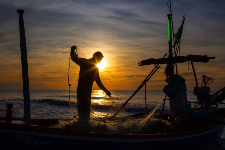 Photo pour silhouette of fisherman with sunrise in the background  - image libre de droit