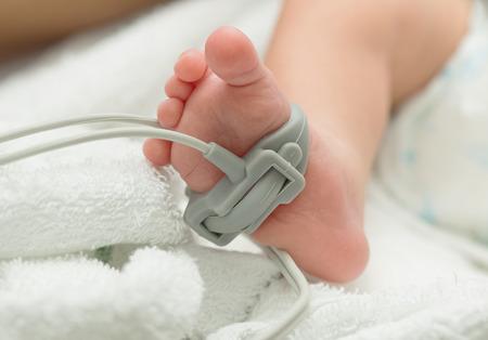 Pulse oximeter sensor on a baby foot , measurement baby patient