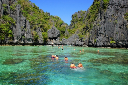 Tourists in lifejackets swimming at lagoon  El Nido, Philippines