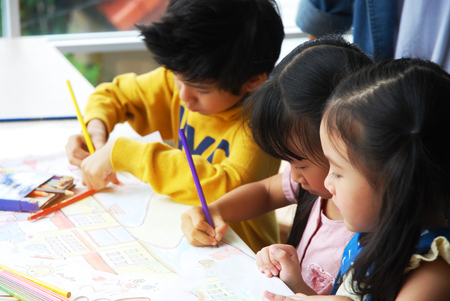 Foto de Teachers are teaching drawing on white paper to three children in holiday weekend. Background blur - Imagen libre de derechos