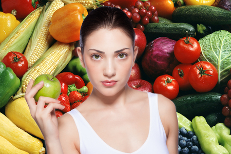 beautiful young woman holding a green apple  Mix of fruit and vegetable in the background