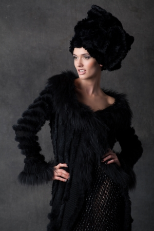 elegant young woman in a black dress with hat