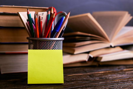 Photo for Notebook, open books and stand for pens on dark wooden table on the background of chalk board. Learning knowledge at school, sticker copy space. - Royalty Free Image