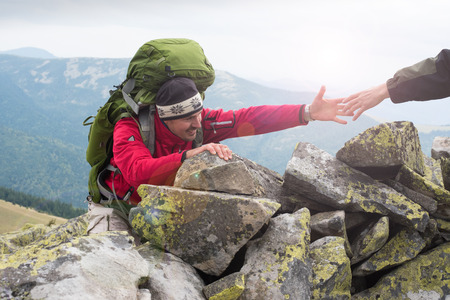 Foto de Helping hand - hiker man getting help on hike smiling happy overcoming obstacle. Hikers climbing on rock, mountain at sunset, one of them giving hand and helping to climb. Help, support, assistance in a dangerous situation. Concept teamwork. - Imagen libre de derechos