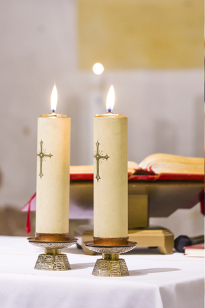 Photo for two candles with a cross light illuminate the church's atre with the blessed gospel, water and wine ready for holy mass - Royalty Free Image