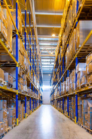 Photo for Interior of a modern warehouse storage with rows and goods boxes on high shelves - Royalty Free Image