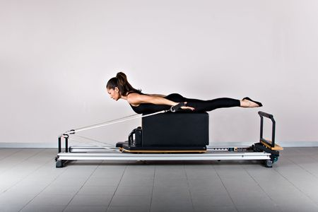 Spine twist and arms exercise. Pilates gymnastics is a Germanic evolution of yoga, used by athletes to improve flexibility and body fitness and by chiropractors for patient recovery.