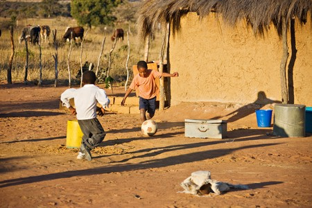 African children playing football at the village cattle post