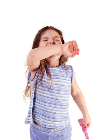young girl sneezing into her arm, isolated