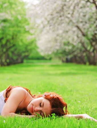 Young pretty girl sleeping in grass