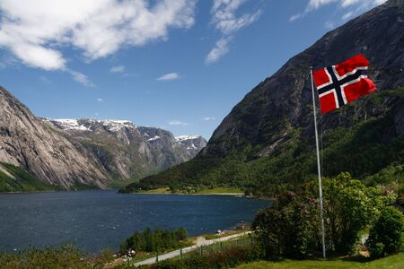Norwegian flag in the foreground. Majestic Hardangerfjord as seen from the village of Eidfjord in the background.