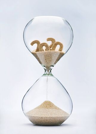 Photo pour New Year 2021 concept. Time running out concept with hourglass falling sand from 2020. - image libre de droit