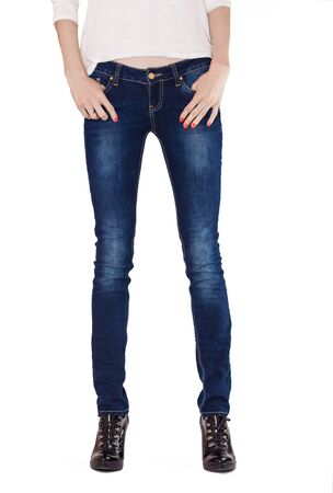 Shapely female legs dressed in dark blue jeans and black varnished boots on white background