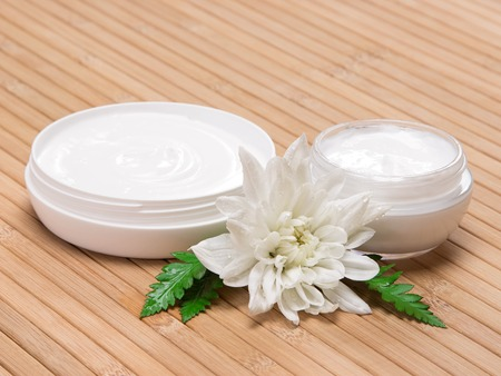 Photo for Natural moisturizing skin care products. Closeup of two open jars filled with cream next to wet white flower and fern leaves on wooden surface - Royalty Free Image