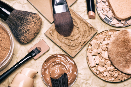 Photo pour Makeup products to even skin tone and complexion on aged paper. Corrector, loose and compact powders, concealer pencil, liquid foundation with brushes and cosmetic sponges. Retro style processing - image libre de droit
