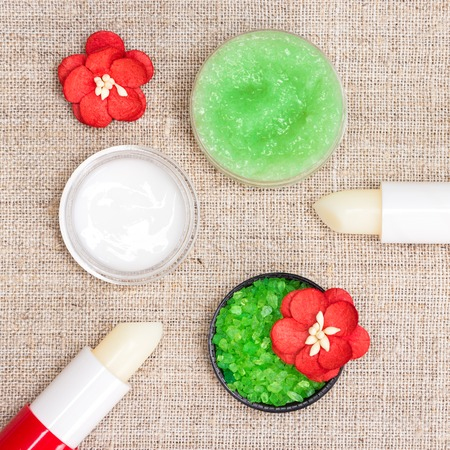 Cosmetics for lip skin care: sea salt, natural honey scrub with essential oils, lip cream and balms with flowers on shabby sackcloth napkin