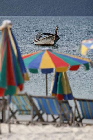 colorfully sun beds,  umbrellas and fishing boat in an island